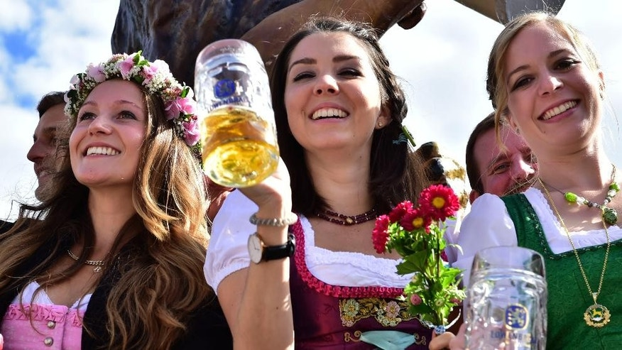 Young women celebrate the opening of the 182.  Oktoberfest beer festival in Munich, southern Germany, Saturday, Sept. 19, 2015. The world's largest beer festival will be held from Sept. 19 to Oct. 4, 2015. (AP Photo/Marc Kleine-Kleffmann)