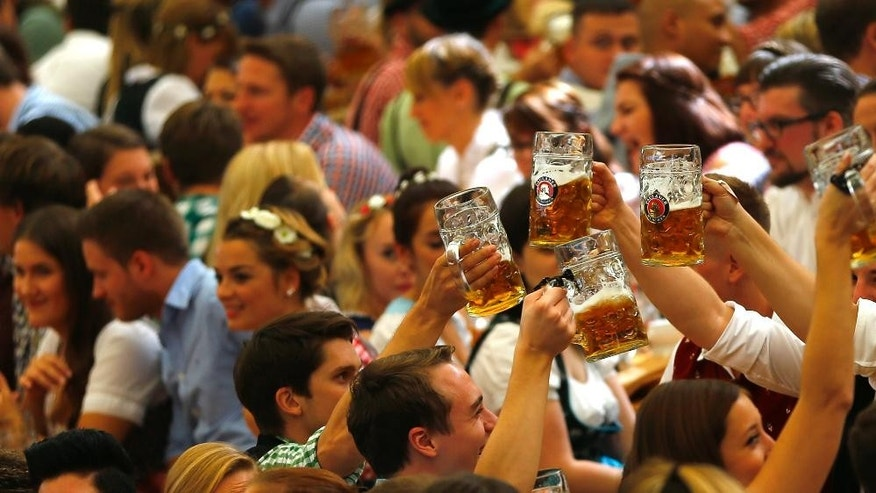 People cheer during  the opening of the 182.  Oktoberfest beer festival in Munich, southern Germany, Saturday, Sept. 19, 2015. The world's largest beer festival will be held from Sept. 19 to Oct. 4, 2015. (AP Photo/Matthias Schrader)
