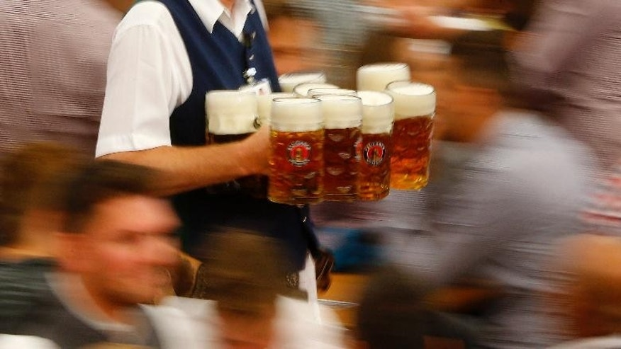 A waiter carries beer mugs during the opening of the 182.  Oktoberfest beer festival in Munich, southern Germany, Saturday, Sept. 19, 2015. The world's largest beer festival will be held from Sept. 19 to Oct. 4, 2015. (AP Photo/Matthias Schrader)