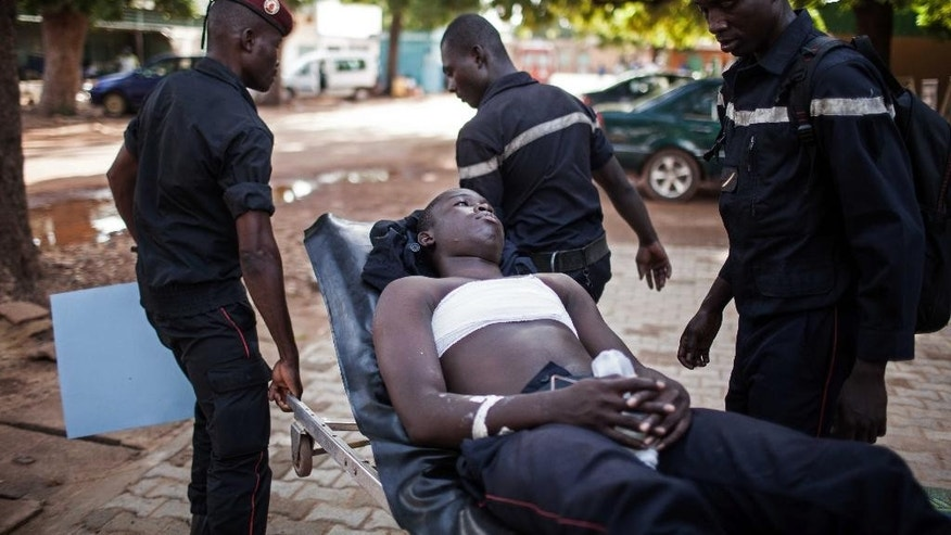 A fireman, center, wounded during a gun battle forming part of the recent coup is carried by fellow fire fighters to hospital for treatment, in Ouagadougou,  Burkina Faso, Friday, Sept. 18, 2015.  Burkina Faso's military on Friday released the country's interim president who was detained during a coup that dissolved his government and soldiers blocked protesters from gathering in the West African nation's capital. (AP Photo/Theo Renaut)