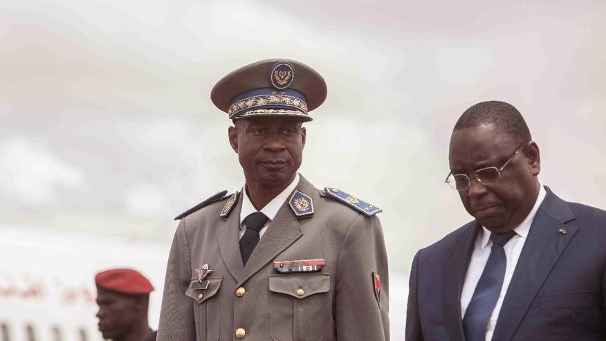 Burkina Faso Gen. Gilbert Diendere, center, walks alongside Senegal President Macky Sall, right, after he arrived at the airport for talks after the recent coup in Ouagadougou, Burkina Faso, Friday, Sept. 18, 2015. Gen. Gilbert Diendere — a former top aide to Compaore who was named on Thursday as the country's military leader — says he already has met with some members of the international community to establish dialogue and to seek a long-term solution.(AP Photo/Theo Renaut)