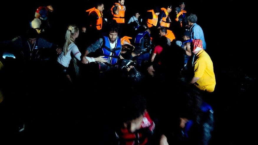 Syrian refugees arrive aboard a dinghy after crossing from Turkey, to the island of Lesbos, Greece, on Saturday, Sept. 19, 2015. A girl about five years old died and at least 13 undocumented refugees and migrants were missing on Saturday after a boat transferring dozens of people from Turkey to Greece overturned off Lesbos island, Greek Coast Guard said. (AP Photo/Petros Giannakouris)