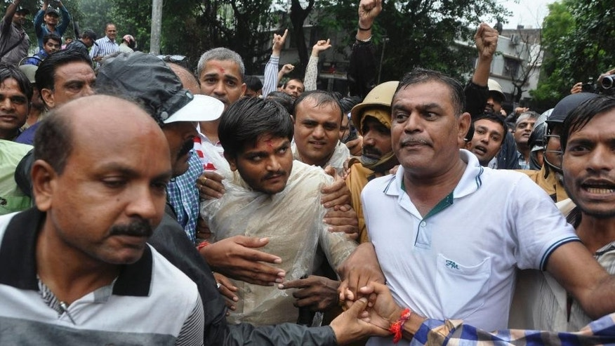 Hardik Patel, center, 22-year-old firebrand leader of Patidar Andolan Samiti walks after he was denied permission to hold a rally in Surat, India, Saturday, Sept. 19, 2015. Police in western Indian detained Patel, the wildly popular leader of a farming caste group Saturday. The Patidars, also known as the Patel community for the last name they share, are demanding they be granted the same special status given to many minorities in India, guaranteeing them a share of government jobs and school places. (AP Photo/Dinesh Trivedi)
