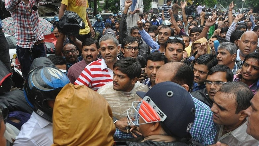 Hardik Patel, center, 22-year-old firebrand leader of Patidar Andolan Samiti walks after he was denied permission to hold a rally in Surat, India, Saturday, Sept. 19, 2015. Sporadic clashes erupted in parts of western India on Saturday after police detained the popular leader of a farming caste group. The Patidars, also known as the Patel community for the last name they share, are demanding they be granted the same special status given to many minorities in India, guaranteeing them a share of government jobs and school places. (AP Photo/Dinesh Trivedi)