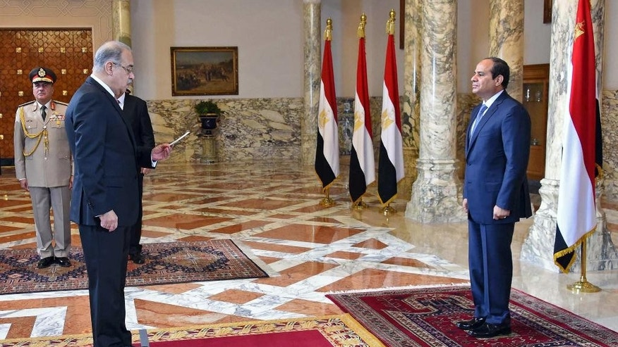 In this photo provided by Egypt's state news agency MENA, Egyptian President Abdel-Fattah el-Sissi, right, presides over the swearing in of Prime Minister Sheriff Ismail one week after the previous Cabinet resigned amid a corruption probe, in Cairo, Egypt, Saturday, Sept. 12, 2015. El-Sissi has also restructured the Cabinet, merging several ministries and forming a new body responsible for immigration, according to the Middle East News Agency. The 33-member Cabinet contains three women and 16 new members. (MENA via AP)