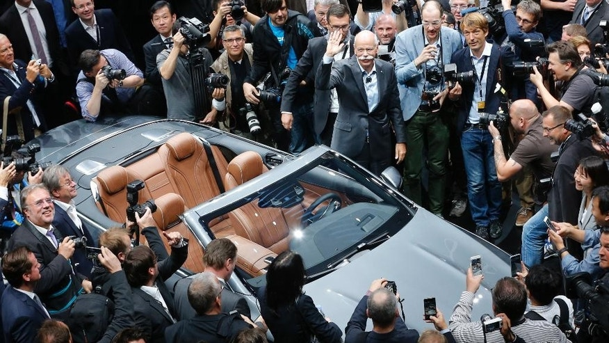 Daimler CEO Dieter Zetsche, top center, waves as he presents the new S-Class Convertible on the first press day of the Frankfurt Auto Show IAA in Frankfurt, Germany, Tuesday, Sept. 15, 2015. The car show runs through Sept. 27. (AP Photo/Michael Probst)