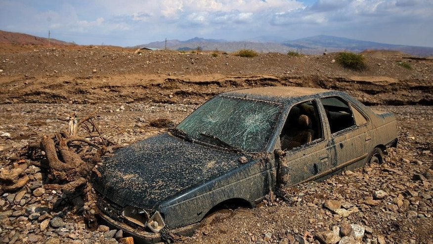 A damaged vehicle is stuck in mud after a flash flood in Pakdasht, southeast of the capital Tehran, Iran, Saturday, Sept. 19, 2015. Iran's state TV says flash floods triggered by heavy rains have killed at least 10 people in the capital, Tehran, and south of the country. Authorities attribute the rising number of deadly flash floods to deforestation and improper construction near riverbeds. (AP Photo/Ebrahim Noroozi)