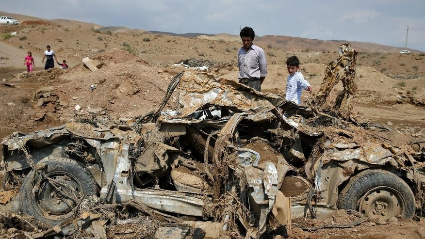Iranians look at the wreckage of a vehicle after a flash flood in Pakdasht, southeast of the capital Tehran, Iran, Saturday, Sept. 19, 2015. Iran's state TV says flash floods triggered by heavy rains have killed at least 10 people in the capital, Tehran, and south of the country. Authorities attribute the rising number of deadly flash floods to deforestation and improper construction near riverbeds. (AP Photo/Ebrahim Noroozi)