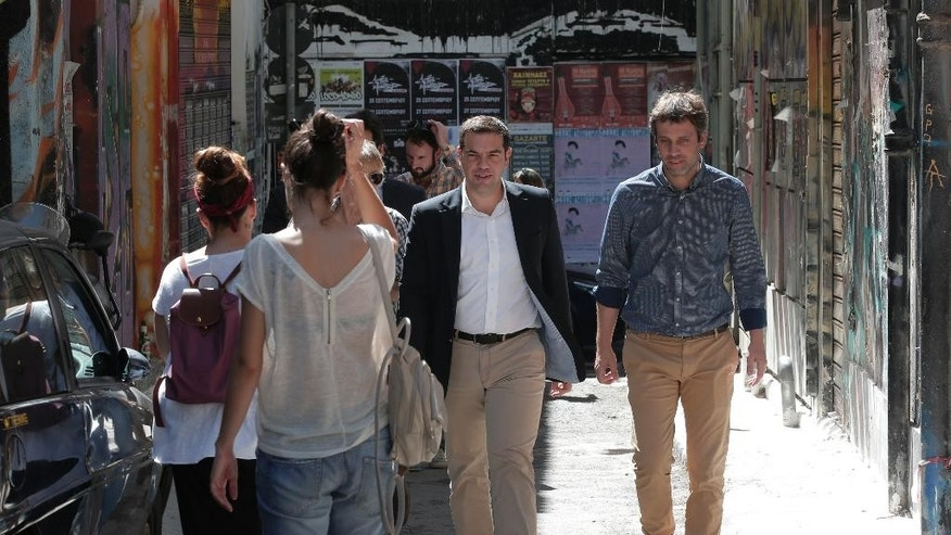 Syriza left-wing party leader and former Prime Minister Alexis Tsipras, centre, walks to a coffee shop to meet with young people in central  Athens, Saturday, Sept. 19, 2015, ahead of Sunday, Sept. 20, 2015 elections. Six years into the country's worst post-World War II financial crisis, Sunday's early parliamentary election is not being fought over austerity, promised debt forgiveness, public sector hirings or tax breaks.  If anything, it's about the dim  prospect of political stability that might help restore some kind of economic normality to a country with 25 percent unemployment, severe banking restrictions and a crippling public debt.  (AP Photo/Lefteris Pitarakis)