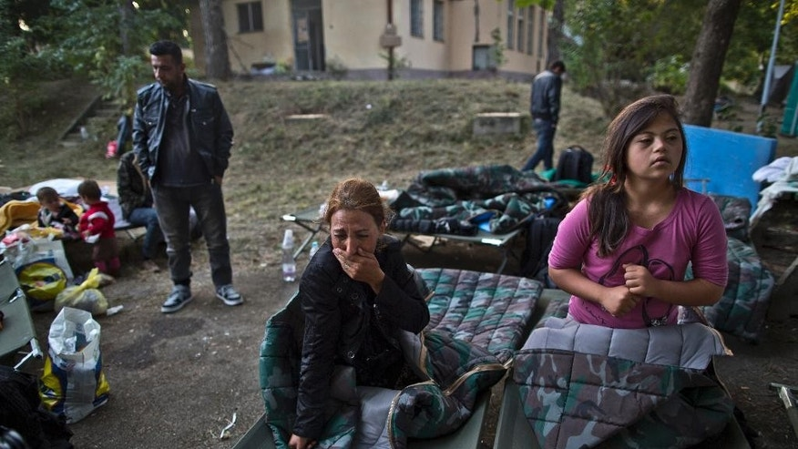 Afghan refugee Mariam Jamshid, 34, from Herat, Afghanistan, cries while talking to a volunteer about her two missing children, after spending the night  near an abandoned military barrack in Beli Manastir, northeast Croatia, near Hungarian border Saturday, Sept. 19, 2015. (AP Photo/Muhammed Muheisen)