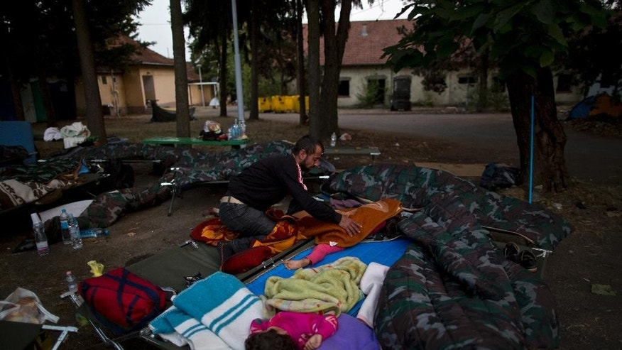 A Yazidi refugee man from Mosul, Iraq, covers his sleeping child near an abandoned military barrack in Beli Manastir, northeast Croatia, near Hungarian border, Saturday, Sept. 19, 2015. (AP Photo/Muhammed Muheisen)