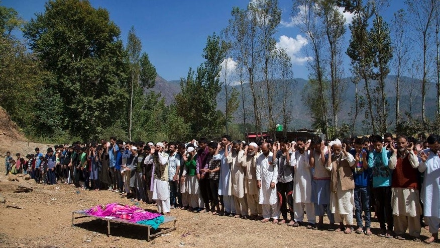 Kashmiri Muslim villagers pray near the  body of a 3-year-old boy during his funeral procession in Sagipora, some 75 kilometers (47 miles) northwest of Srinagar, Indian controlled Kashmir, Saturday, Sept. 19, 2015. Gunmen have shot and killed the 3-year-old boy and his father in Indian-controlled Kashmir, police said Saturday. (AP Photo/Dar Yasin)