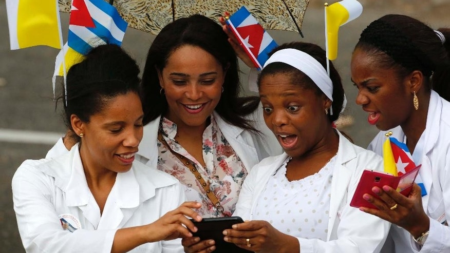 Medical staff from a nearby hospital, wearing Vatican and Cuban flags in their hair, look at pictures on their mobile phone while waiting for Pope Francis' motorcade in Havana, Cuba, Saturday, Sept. 19, 2015. Pope Francis began his 10-day trip to Cuba and the United States, embarking on his first trip to the onetime Cold War foes after helping to nudge forward their historic rapprochement. (AP Photo/Desmond Boylan)