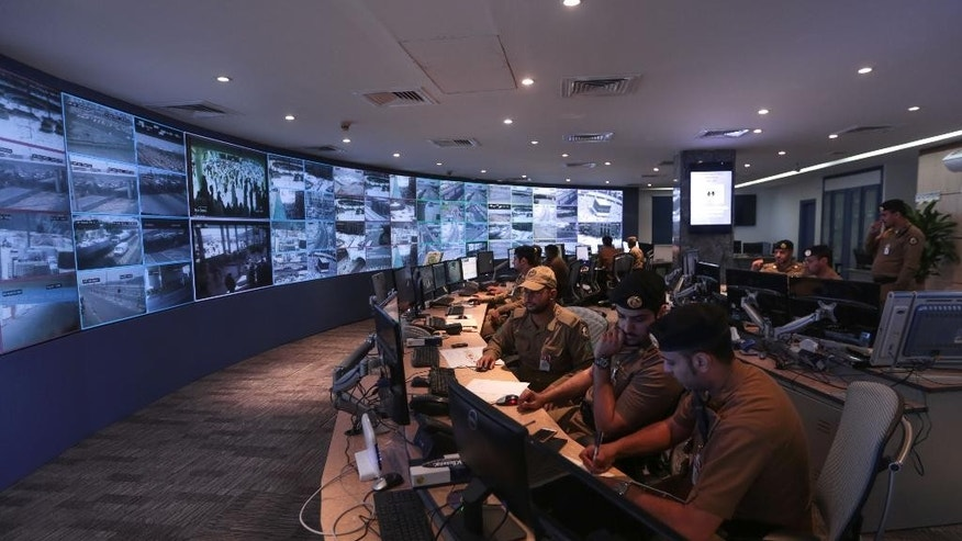 Saudi security officers monitor screens with live views of Muslim pilgrims in the holy city of Mecca, along with highways and high density areas, a few days before the start of the annual pilgrimage, known as the hajj, in Mecca, Saudi Arabia, Saturday, Sept. 19, 2015. (AP Photo/Mosa'ab Elshamy)