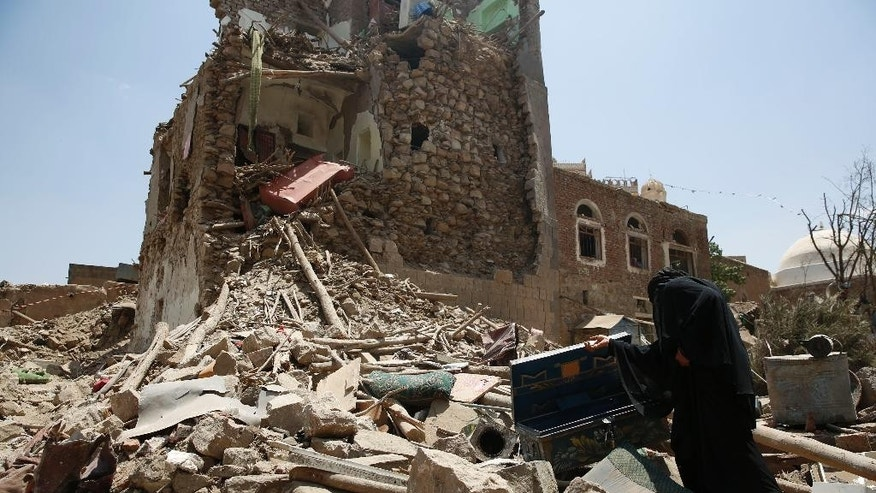 A woman searches in the rubble from a house damaged in a Saudi-led airstrike in Sanaa, Yemen, Saturday, Sept. 19, 2015. The airstrikes against Yemen's Shiite rebels and their allies have killed almost 30  people, including civilians, in the capital Sanaa, security and medical officials there said Saturday. The coalition's overnight airstrikes hit an apartment building in the center of the capital, a UNESCO world heritage site, killing a family of nine, the officials who remain neutral in the conflict that has divided Yemen's security forces said. (AP Photo/Hani Mohammed)