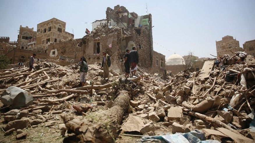 People stand amid the rubble of a house damaged in a Saudi-led airstrike in Sanaa, Yemen, Saturday, Sept. 19, 2015. The overnight airstrikes against Yemen's Shiite rebels and their allies have killed almost 30 people, including civilians, in the capital Sanaa, security and medical officials there said Saturday. The coalition's airstrikes hit an apartment building in the center of the capital, a UNESCO world heritage site, killing a family of nine, the officials who remain neutral in the conflict that has divided Yemen's security forces said. (AP Photo/Hani Mohammed)