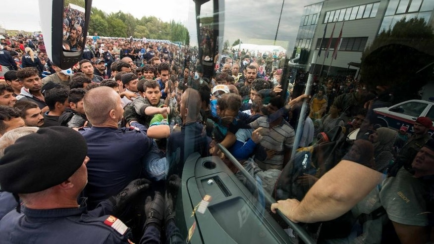 Migrants enter a buss after they arrived at the border between Austria and Hungary near Heiligenkreuz, about 180 kms (110 miles) south of Vienna, Austria, Saturday, Sept. 19, 2015.  Thousands of migrants who had been stuck for days in southeastern Europe started arriving in Austria early Saturday after Hungary escorted them to the border. (AP Photo/Christian Bruna)