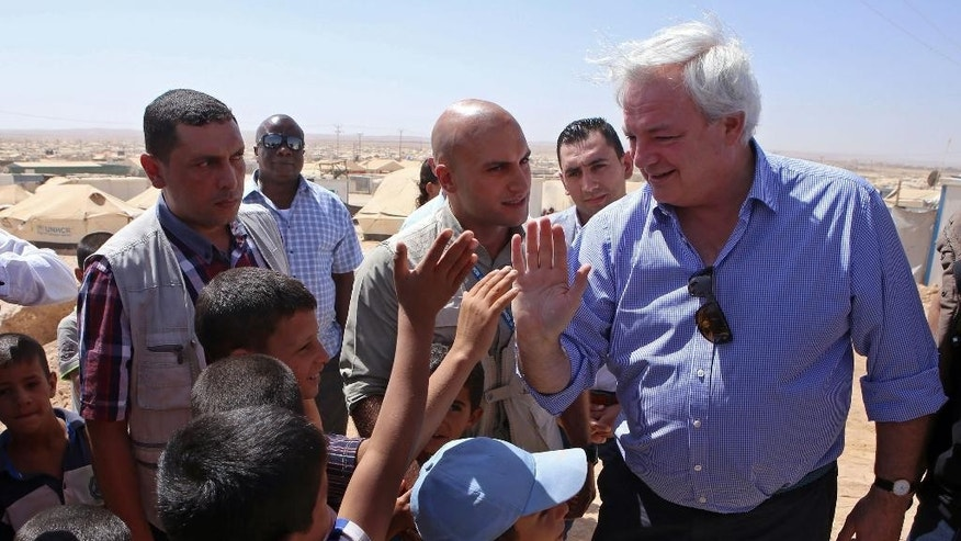 "U.N. humanitarian chief  Stephen O'Brien, right, greets Syrian refugees who fled civil war in their country, in the Zaatari Refugee Camp, near Mafraq, Jordan, Saturday, Sept. 19, 2015. O'Brien said the international community has sent ""record amounts'' of aid to alleviate the fallout from the Syria crisis, but that it's hard to keep up with rising regional needs. Some 4 million people have fled Syria since 2011, most moving to neighboring countries. (AP Photo/Raad Adayleh)"