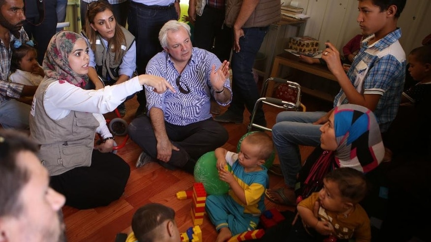 "U.N. humanitarian chief  Stephen O'Brien, center, visits with Syrian refugees who fled civil war in their country, in the Zaatari Refugee Camp, near Mafraq, Jordan, Saturday, Sept. 19, 2015. O'Brien said the international community has sent ""record amounts'' of aid to alleviate the fallout from the Syria crisis, but that it's hard to keep up with rising regional needs. Some 4 million people have fled Syria since 2011, most moving to neighboring countries. (AP Photo/Raad Adayleh)"
