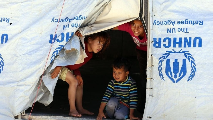 "Syrian refugee children look from their tent during a visit by U.N. humanitarian chief Stephen O'Brien to the Zaatari Refugee Camp, near Mafraq, Jordan, Saturday, Sept. 19, 2015. O'Brien said the international community has sent ""record amounts'' of aid to alleviate the fallout from the Syria crisis, but that it's hard to keep up with rising regional needs. Some 4 million people have fled Syria since 2011, most moving to neighboring countries. (AP Photo/Raad Adayleh)"