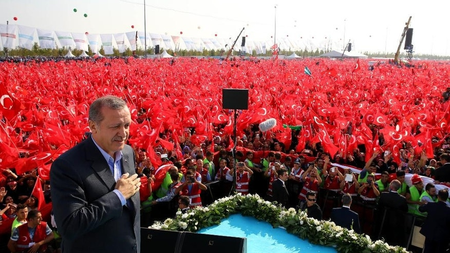 Turkey's President Recep Tayyip Erdogan salutes supporters as tens of thousands of flag-waving demonstrators rally to denounce violence by Kurdish rebels, in Istanbul, Turkey, Sunday, Sept. 20, 2015. Speakers condemned terrorism and the violence which has rocked eastern Turkey since the resumption of fighting between the military and the Kurdistan Workers' Party, or PKK. The separatist group is considered a terror organization by the Turkey, the U.S. and the EU.(Presidential Press Service/Pool photo via AP)