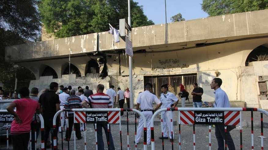 Egypt's security forces stand guard at the site of an explosion that damaged a nearby building with administrative offices for Egypt's Ministry of Foreign Affairs in Cairo, Egypt, Sunday, Sept. 20, 2015. Egypt's state news agency MENA said a few people were injured when a bomb exploded in a middle-class neighborhood of Cairo. (AP Photo/Mohammed Abu Zaid)