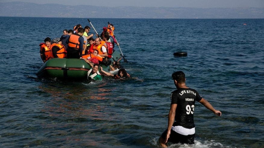 Migrant whose boat stalled at sea while crossing from Turkey to Greece approach the shore of the island of Lesbos, Greece, on Sunday, Sept. 20, 2015. A boat with 46 migrants or refugees has sunk Sunday in Greece and the coast guard says it is searching for 26 missing off the eastern Aegean island of Lesbos. (AP Photo/Petros Giannakouris)