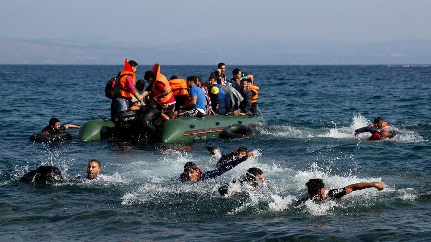 Migrant whose boat stalled at sea while crossing from Turkey to Greece swim to approach the shore of the island of Lesbos, Greece, on Sunday, Sept. 20, 2015. A boat with 46 migrants or refugees has sunk Sunday in Greece and the coast guard says it is searching for 26 missing off the eastern Aegean island of Lesbos. (AP Photo/Petros Giannakouris)