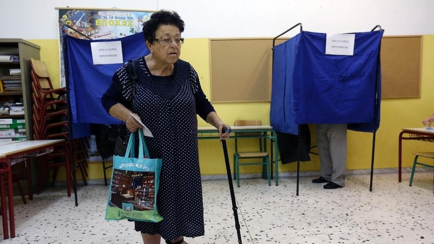An elderly woman casts her vote at a polling station in Athens, Sunday, Sept. 20, 2015. Greeks were voting Sunday in their third national polls this year, called on to choose who they trust to steer the country into its new international bailout. (AP Photo/Thanassis Stavrakis)