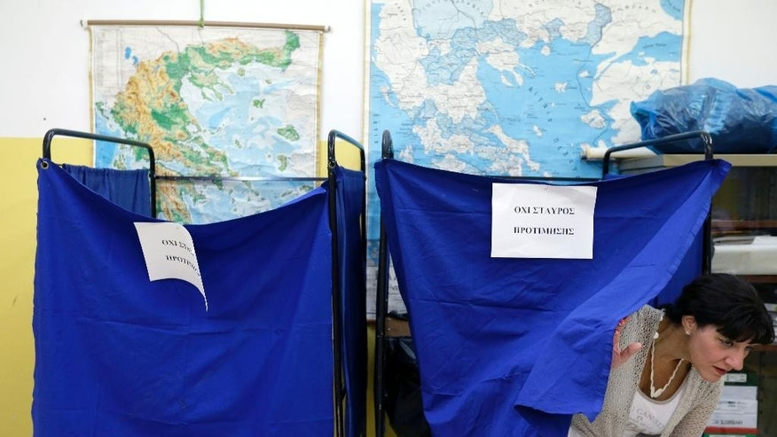 A woman casts her vote at a polling station in Athens, Sunday, Sept. 20, 2015. Greeks were voting Sunday in their third national polls this year, called on to choose who they trust to steer the country into its new international bailout. (AP Photo/Thanassis Stavrakis)