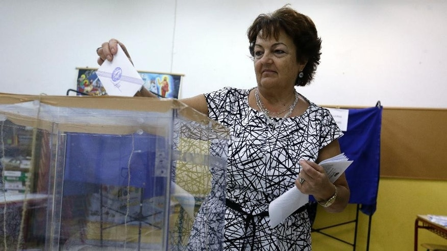 A woman casts his vote at a polling station in Athens, Sunday, Sept. 20, 2015. Greeks were voting Sunday in their third national polls this year, called on to choose who they trust to steer the country into its new international bailout. (AP Photo/Thanassis Stavrakis)