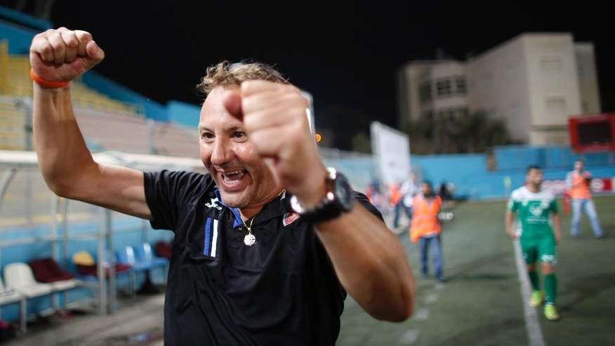 "In this Friday, Sept. 11, 2015 photo, Italian Stefano Cusin, soccer coach of the Palestinian al-Ahli al-Khalil football club reacts during the ""Super Cup"" match against al-Dahria at the Faisal al-Husseini Stadium in the West Bank town of Al-Ram, north of Jerusalem. Throughout his long career, Cusin has played in Italy, France and Switzerland and coached in Bulgaria, Cameroon and the Congo. But the 46-year-old, Tuscany-born Cusin says it's only in the Palestinian soccer backwater of Hebron that he's truly rediscovered his passion for the sport. (AP Photo/Nasser Shiyoukhi)"