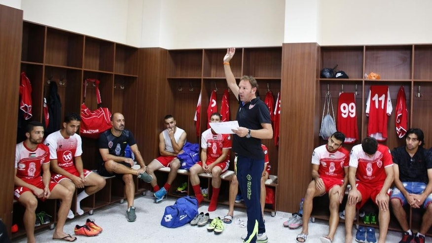 "In this Friday, Sept. 11, 2015 photo, Italian Stefano Cusin, coach of the Palestinian Ahli Al-Khalil football club, speaks to the players during the ""Super Cup"" match against al-Dahria at the Faisal al-Husseini Stadium in the West Bank town of Al-Ram, north of Jerusalem. Throughout his long career, Cusin has played in Italy, France and Switzerland and coached in Bulgaria, Cameroon and the Congo. But the 46-year-old, Tuscany-born Cusin says it's only in the Palestinian soccer backwater of Hebron that he's truly rediscovered his passion for the sport. (AP Photo/Nasser Shiyoukhi)"