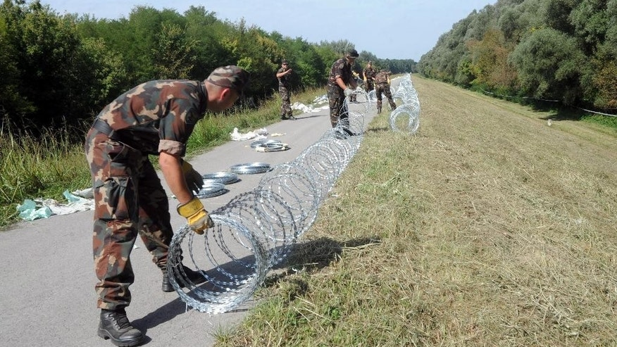 "Hungarian soldiers set up razor wire, the first line of a temporary fence under construction on Hungary's southern border with Croatia destined to halt illegal migrants entering the country's territory from Croatia near Kolked, 215 kms south of Budapest, Hungary, Friday, Sept. 18, 2015. Hungary has begun to build a fence on the border with Croatia and will set up a ""transit zone"" near the village of Beremend where migrants entering from Croatia can request asylum. (Peter Lendvai/MTI via AP)"