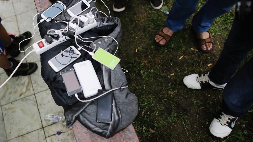Refugees stand around a multiple power socket and charge their mobile devices as they wait to cross the border into Slovenian at the village of Harmica in Croatia, Sunday, Sept. 20, 2015. The refugees wait to enter Slovenia and virtually all are hoping to move on to wealthier EU nations like Germany or Sweden. (AP Photo/Markus Schreiber)