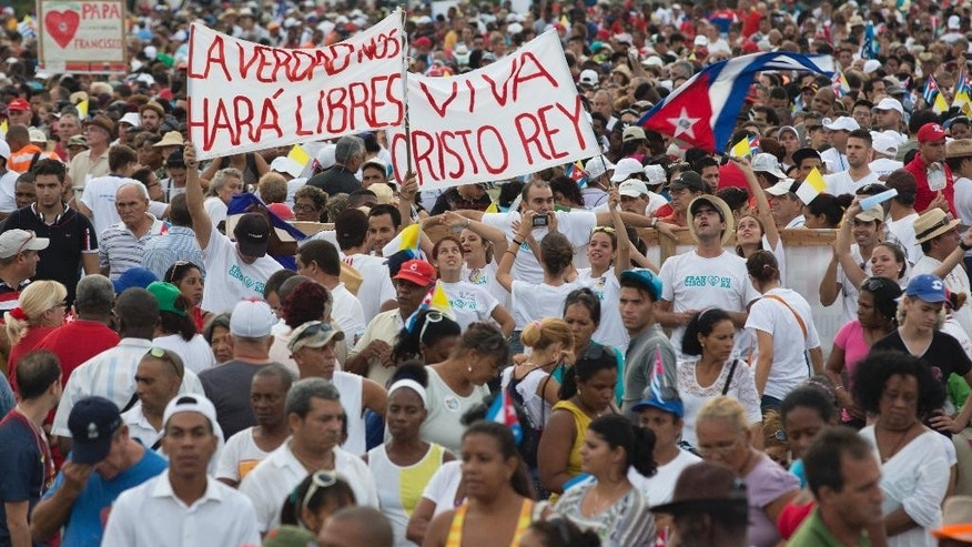 "Faithful wait the arrival of Pope Francis for Mass in Revolution Plaza in Havana, Cuba, Sunday, Sept. 20, 2015.  Pope Francis opens his first full day in Cuba on Sunday with what normally would be the culminating highlight of a papal visit: Mass before hundreds of thousands of people in Havana's Revolution Plaza. The signs in Spanish read: ""The truth will set us free,"" left, and ""Long live Christ the king."" (AP Photo/Enric Marti)"