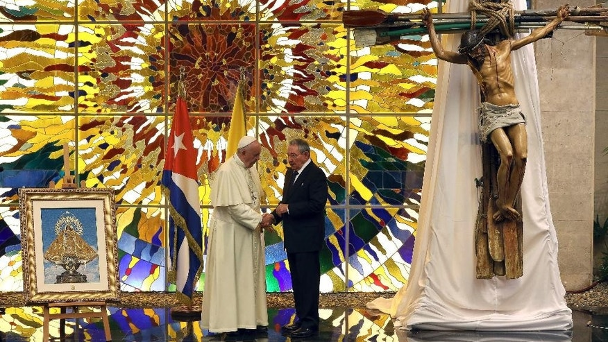 Cuban President Raul Castro shows Pope Francis what appear to be official gifts for the pontiff on display inside the Palace of the Revolution: a huge crucifix made of oars and a painting of the Virgin of Charity of Cobre, Cuba's patron saint, in the Revolution Palace in Havana, Cuba, Sept. 20, 2015. Francis and Castro met in Cuba's seat of government for a state meeting. (Alejandro Ernesto/Pool via AP)