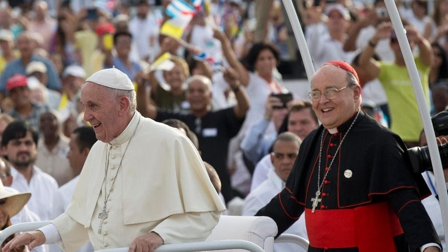 Cuba's Cardinal Jaime Ortega, right, stands behind Pope Francis in the popemobile as they arrive for Mass at Revolution Plaza in Havana, Cuba, Sunday, Sept. 20, 2015. During Mass Sunday, Ortega thanked the pope for his work promoting detente between Havana and Washington and called for reconciliation between Cubans living on the island and elsewhere. Ortega was among many priests sent to military-run agricultural camps in the 1960s after Fidel Castro declared Cuba to be socialist and accused prominent Catholics of trying to topple him. (Ismael Francisco/Cubadebate Via AP)