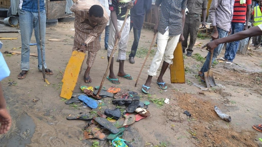 People gathered shoes  at the site of last night's explosion in Maiduguri, Nigeria Monday, Sept. 21, 2015. Extremists detonated three explosive devices in Maiduguri, the capital of Borno state, in Nigeria's northeast, a military official said Sunday. (AP Photo/Jossy Ola)