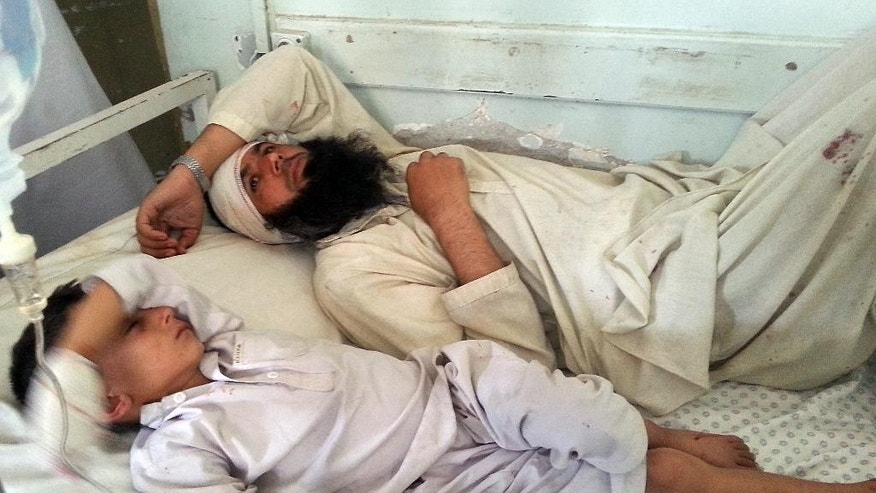 A wounded Afghan man and a child lie on a bed after they were wounded in an explosion in Kunar province, Afghanistan, Sunday, Sept. 20, 2015. An Afghan official says several people, including two police officers, were wounded in a suicide attack near Kandahar on Sunday. More than a dozen civilians were wounded after a bomb hidden near an electric station exploded in eastern Kunar province, said Gen. Abdul Habib Sayedkhaili, the provincial police chief. (AP Photo)