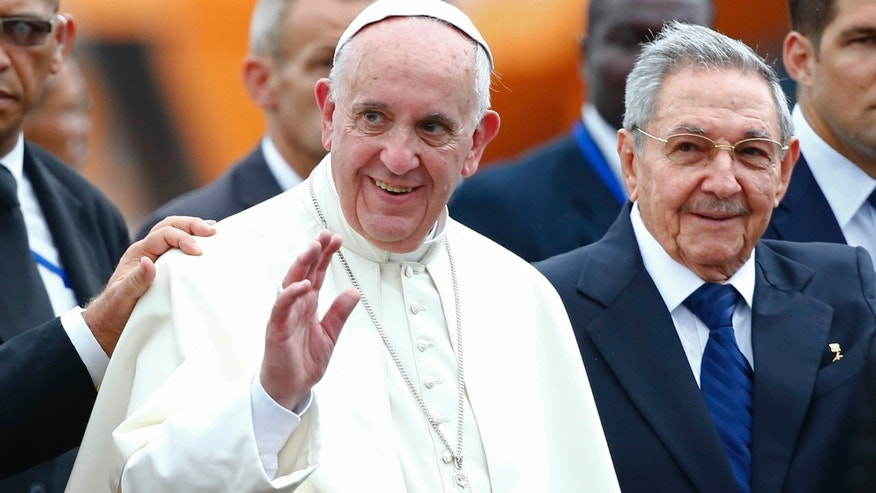 Sept. 19, 2015: Pope Francis waves next to Cuba's President Raul Castro during his arrival ceremony at the airport in Havana, Cuba.