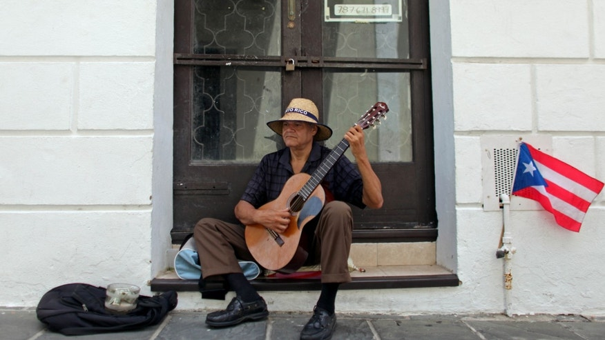 A man plays his guitar while he begs for money in front of a closed down business in Old San Juan, Puerto Rico, Monday, June 29, 2015. International economists released a critical report on Puerto Rico's economy Monday on the heels of the governor's warning that the island can't pay its $72 billion public debt. (AP Photo/Ricardo Arduengo)