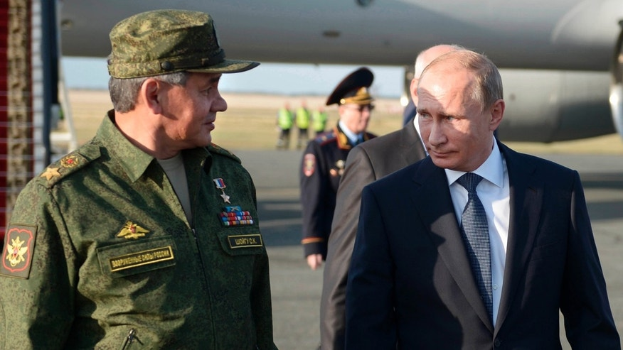 Sept. 19, 2015: Russian President Vladimir Putin speaks with Defense Minister Sergei Shoigu on his arrival in Orenburg region, about 800 miles southeast of Moscow, Russia.
