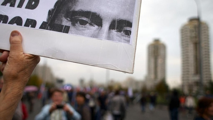 A protester holds a poster with portrait of Russian President Vladimir Putin during an opposition rally in Moscow, Russia, on Sunday, Sept. 20, 2015. Russia's opposition rallied in an outlying Moscow neighborhood to decry the rule of President Vladimir Putin. (AP Photo/Ivan Sekretarev)