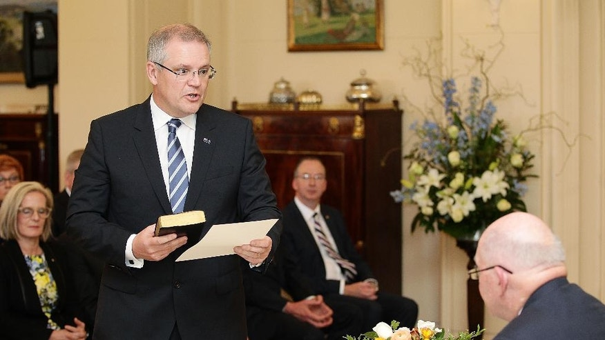 FILE - In this Monday, Sept. 21, 2015, file photo, Australia's Treasurer Scott Morrison, left, is sworn in by Governor-General Peter Cosgrove, right, during the swearing-in ceremony of Prime Minister Malcolm Turnbull's cabinet at Government House in Canberra, Australia. Turnbull received a boost from a respected opinion poll on Tuesday, Sept. 22, 2015, but the fallout lingers from a bitter party battle as the leader he ousted has attacked the credibility of Morrison. A Newspoll published in The Australian newspaper on Tuesday found that Turnbull is Australia's most popular prime minister in more than five years - a period that covered the terms of Julia Gillard, Kevin Rudd and Tony Abbott. (Stefan Postles/Pool Photo via AP, File)