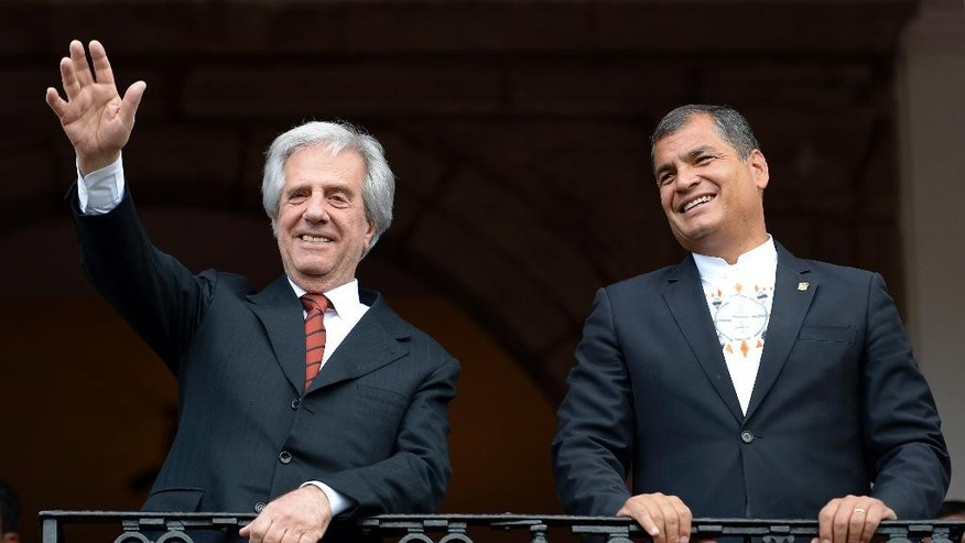 Uruguay's President Tabare Vazquez waves from a government palace balcony, accompanied by Ecuador's Rafael Correa, in Quito, Ecuador, Monday, Sept. 21, 2015. The leaders of Colombia and Venezuela are traveling to Ecuador on Monday in a bid to overcome a monthlong border crisis that has paralyzed trade and movement along the frontier. (AP Photo/Patricio Realpe)