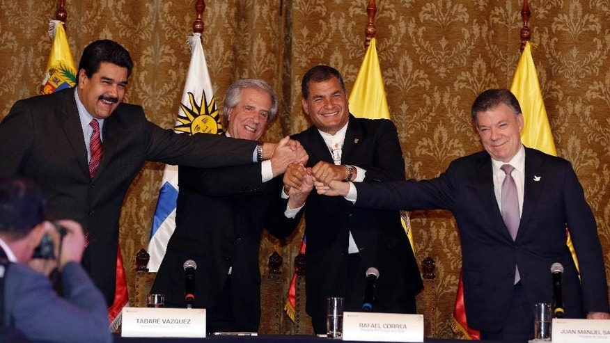 The presidents of Venezuela Nicolas Maduro, left, Uruguay Tabare Vazquez, second left, Ecuador Rafael Correa, second right, and Colombia Juan Manuel Santos shake hands at the end the meeting in Quito, Ecuador, Monday, Sept. 21, 2015. The presidents of Colombia and Venezuela met in Ecuador's capital to talk about month long fight over Venezuela's anti-smuggling crackdown that has left the border between the two countries closed and resulted in the deportation of some 1,500 Colombians. (AP Photo/Dolores Ochoa)
