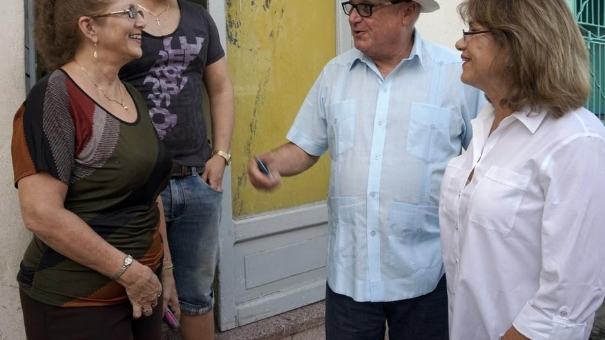 Berta Luisa Fernandez, left, and her son, Daniel Jose Pupo Fernandez, reunite with cousin Olga Maria Saladrigas, and her husband, Carlos Saladrigas, in Holguin, Cuba, Monday, Sept. 21, 2015. After Fidel Castro's 1959 revolution, Saladrigas' family decided they disagreed with the country's new socialist system and fled to Miami. Fernandez's father backed the revolution and decided they would stay. The cousins reunited for the third time in 50 years, (AP Photo/Christine Armario)