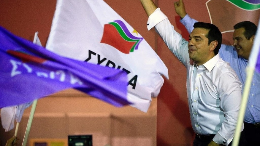 Left-wing Syriza party leader Alexis Tsipras, left, waves to his supporters as leader of the right-wing Independent Greeks party Panos Kammenos makes the victory sign after his general election victory, at Syriza's party's main electoral center in Athens, Sunday, Sept. 20, 2015. Tsipras said he would renew his partnership with Kammenos in coalition government. (AP Photo/Lefteris Pitarakis)