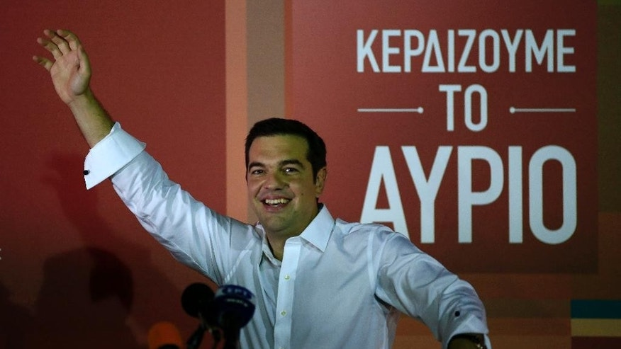 Alexis Tsipras, head of the left-wing Syriza party waves to his supporters after his general election victory, at Syriza's party's main electoral center in Athens, Sunday, Sept. 20, 2015. Tsipras who won Greece's parliamentary election for the second time this year on Sunday, says he will form a coalition government with the small right-wing Independent Greeks. The sign reads in Greek ''We win tomorrow.'' (AP Photo/Lefteris Pitarakis)